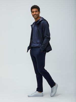 Men's Navy Doppler Packable Jacket layered over Men's Cadet Blue Composite Merino Henley with Men's Navy Fusion pant on model walking left with hands in pockets