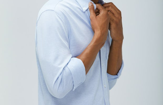 men's blue heather stripe hybrid button down zoomed shot of model facing right with sleeves cuffed