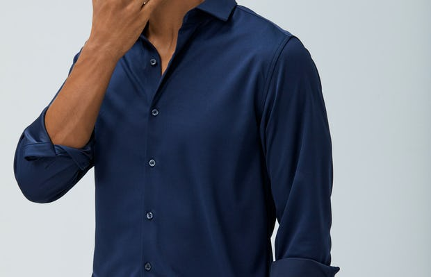 men's navy non brushed apollo dress shirt model facing forward sleeves rolled hand on chin