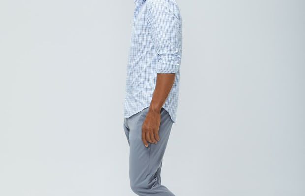men's blue tattersall aero zero dress shirt and light grey momentum chino sleeves rolled model facing to the side