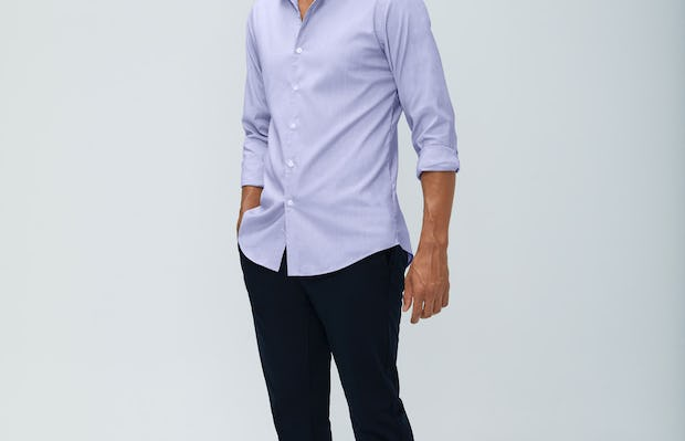 Men's lavender end on end aero dress shirt and navy kinetic pant model facing forward sleeves rolled hand in pocket