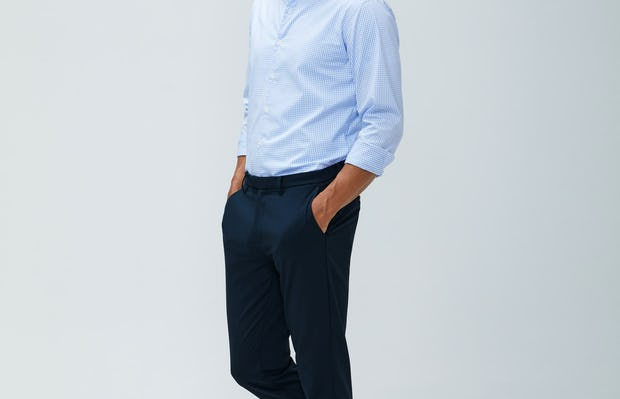 Men's sky blue grid aero dress shirt and navy kinetic pant model facing to the side with hands in pockets