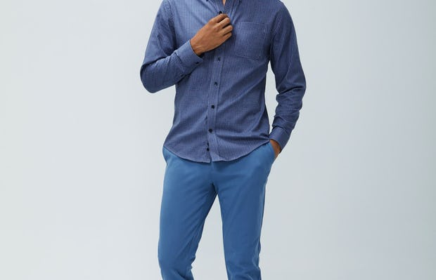 Men's indigo heather gingham aero button down and storm blue momentum chino model facing forward with hand in pocket