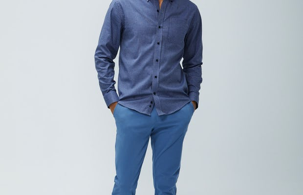 Men's indigo heather gingham aero button down and storm blue momentum chino model facing forward with hands in pockets