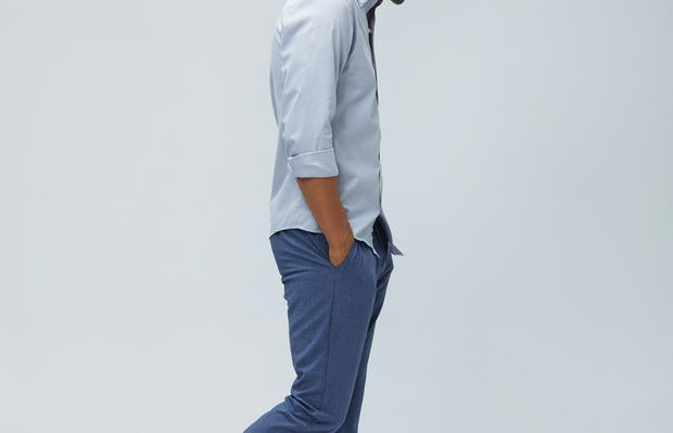 Men's grey heather houndstooth aero button down and calcite heather velocity pant model facing to the side with sleeves rolled hands in pockets