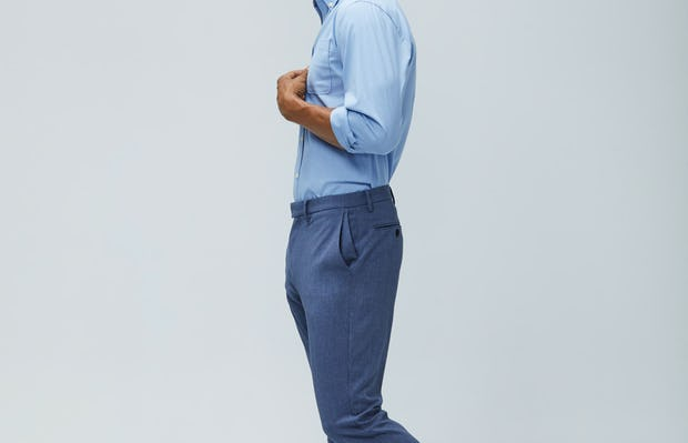 Men's chambray mini grid aero button down calcite heather velocity pant model facing to the side shirt tucked sleeves rolled