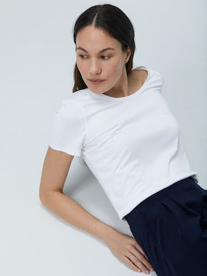Close up of Women's White Luxe Touch Tee on Model laying back
