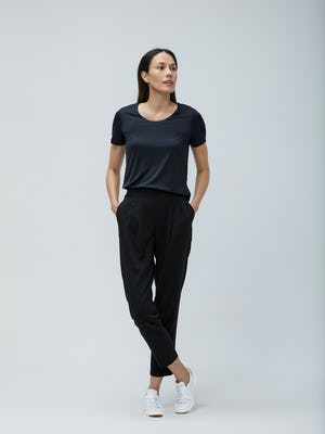 Women's Black Luxe Touch Tee and Women's Black Swift Drape Pant on model facing forward with legs crossed