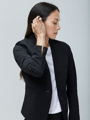 Women's Black Kinetic Blazer and White Luxe Touch Tank on Model adjusting hair
