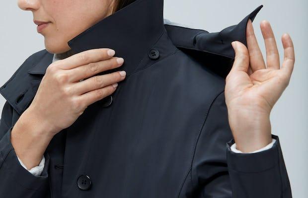 Close up of Women's Black Doppler Mac on model removing hood
