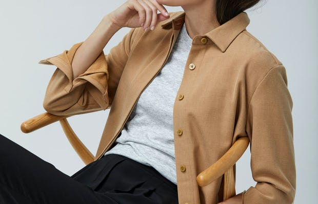 Women's Camel Fusion Overshirt layered over Light Grey Composite Merino Tee and Women's Black Swift Drape Pant on Model sitting in chair