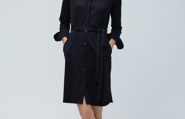 Women's Black Apollo Shirt Dress on Model facing forward with legs crossed
