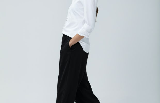 Women's White Aero Zero Dress Shirt and Women's Black Swift Wide Leg Pant on Model walking left