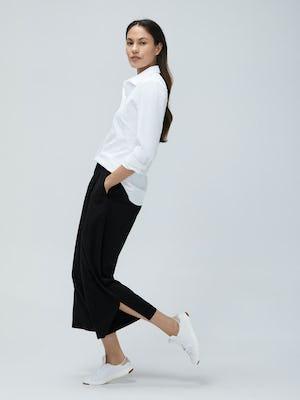 Women's White Aero Zero Dress Shirt and Women's Black Swift Wide Leg Pant on Model walking left and leaning back