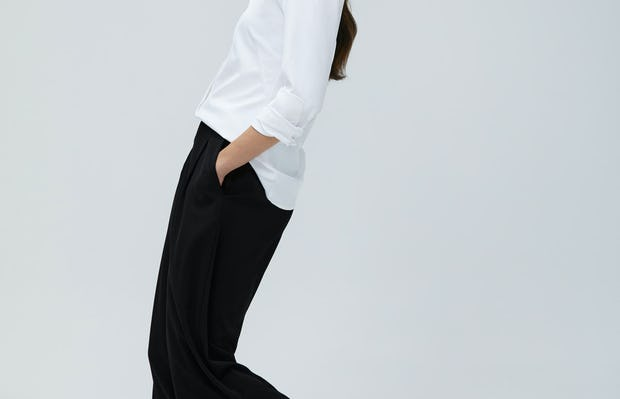 Women's White Aero Zero Dress Shirt and Women's Black Swift Wide Leg Pant on Model walking left and leaning back