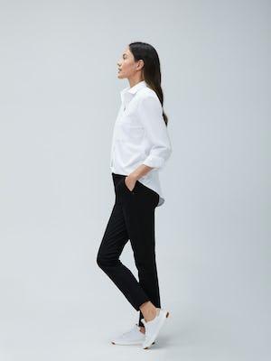 Women's White Aero Zero Boyfriend Shirt and Women's Black Kinetic Slim Pants on Model facing left with legs crossed