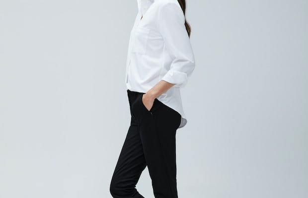 Women's White Aero Zero Boyfriend Shirt and Women's Black Kinetic Slim Pants on Model facing left with legs crossed