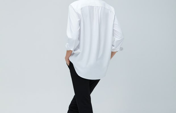 Women's White Aero Zero Boyfriend Shirt and Women's Black Kinetic Slim Pants on model facing backward with crossed legs