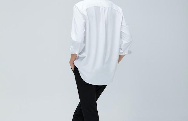 Women's White Aero Zero Boyfriend Shirt and Women's Black Kinetic Slim Pants on model facing backward with crossed legs
