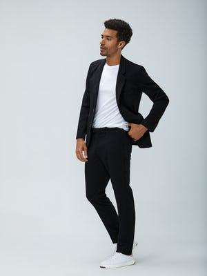 Men's Black Velocity Blazer and Black Velocity Pant with Men's White Atlas Crew Neck Tee on Model facing left adjusting waistband