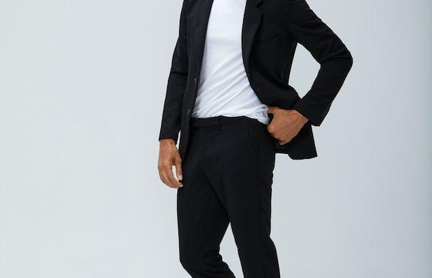 Men's Black Velocity Blazer and Black Velocity Pant with Men's White Atlas Crew Neck Tee on Model facing left adjusting waistband