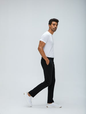 Men's White Atlas Crew Neck Tee and Men's Black Velocity Pant on model walking right with hand in pant pocket