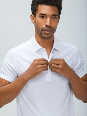 Close up of Men's White Apollo Polo on model adjusting button