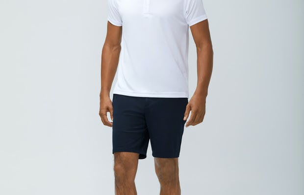 Men's White Apollo Polo  and Men's Navy Kinetic Shorts on model walking forward