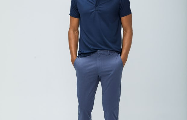 Men's Navy Apollo Polo and Men's Indigo Heather Kinetic Pant on model facing forward with hands in pants pockets