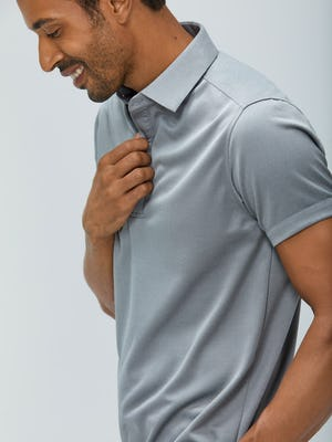 Close up of Men's Charcoal Heather Apollo Polo on model facing left adjusting buttons