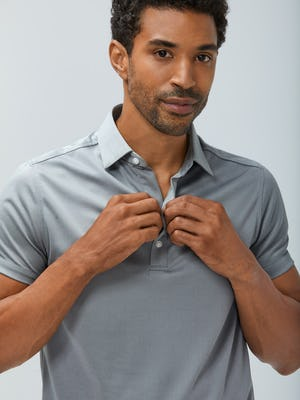 Close up of Men's Charcoal Heather Apollo Polo on model facing forward adjusting buttons