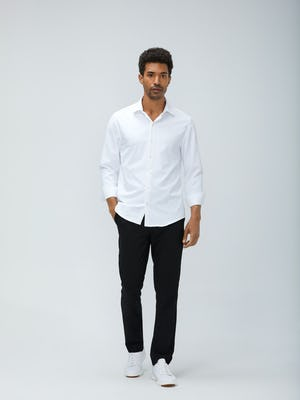Men's White Aero Zero Dress Shirt and Men's Black Velocity Pant on Model walking forward with hand in pant pocket