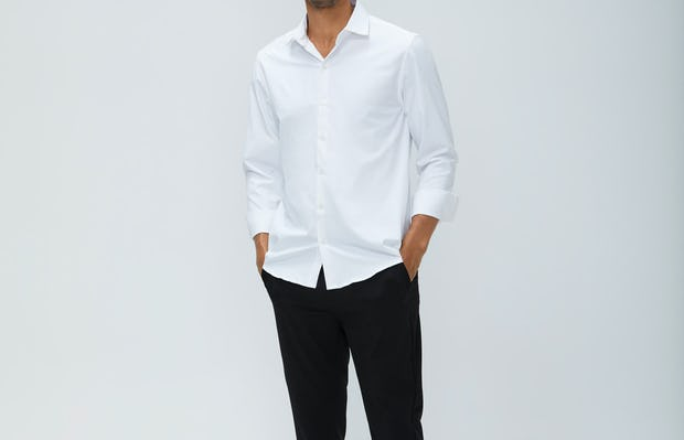 Men's White Aero Zero Dress Shirt and Men's Black Velocity Pant on Model facing forward with hands in pants pockets