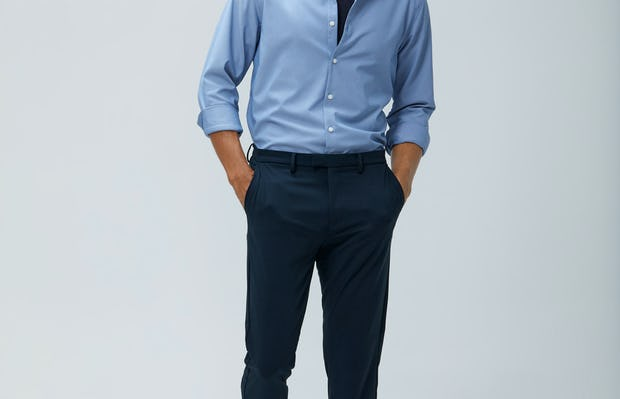Men's Blue Oxford Aero Zero Dress Shirt and Men's Dark Navy Velocity Pant on model walking forward with hands in pants pockets