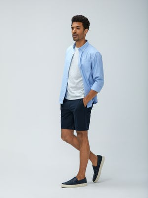 Men's Blue Oxford Aero Zero Dress Shirt and Men's Navy Kinetic Shorts on model walking left with hands in shorts pockets
