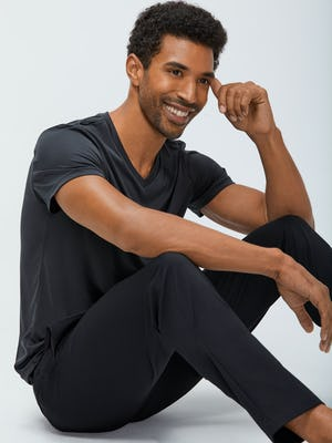 Men's Black Kinetic Pant with Men's Black Responsive V-Neck Tee on Model sitting down