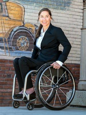 model wearing women's kinetic black kinetic adaptive pants sitting in wheelchair outside facing left