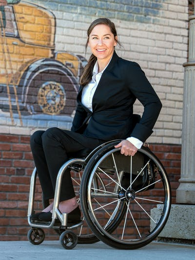 model wearing women's kinetic black kinetic adaptive pants sitting in wheelchair outside facing left