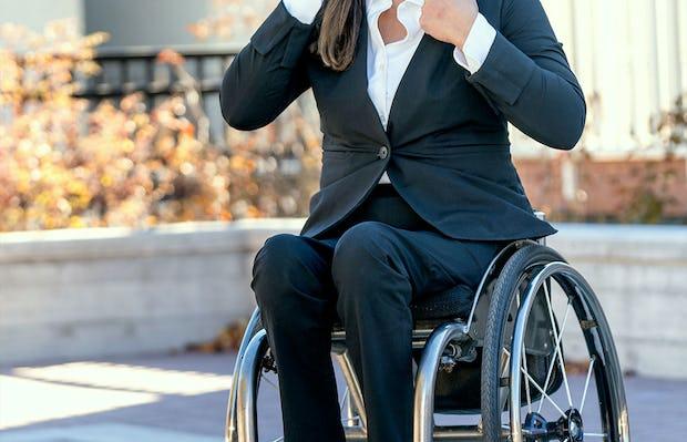 model wearing women's kinetic black kinetic adaptive pants sitting in wheelchair outside facing forward