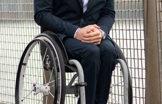 model wearing men's kinetic navy kinetic adaptive pants sitting in wheelchair outside facing forward