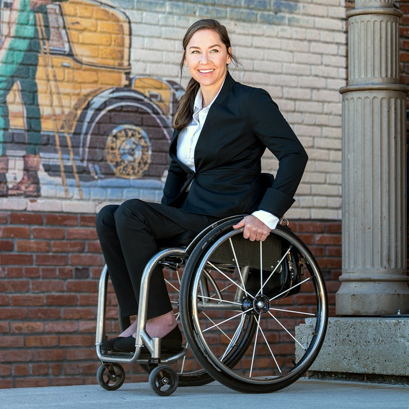 Alana Nichols wearing the Kinetic Suit while seated in a wheelchair