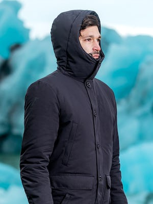 zoomed shot of model wearing great auk down-less parka zipped facing to the side with hood up