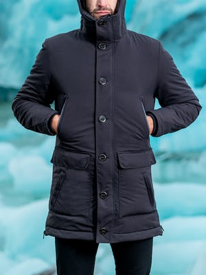 zoomed shot of model wearing great auk down-less parka zipped facing forward hands in upper pockets