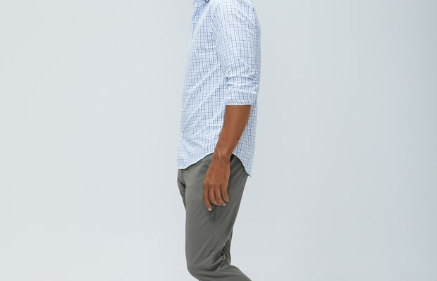 men's blue tattersall aero zero dress shirt and men's sage momentum chino model walking left