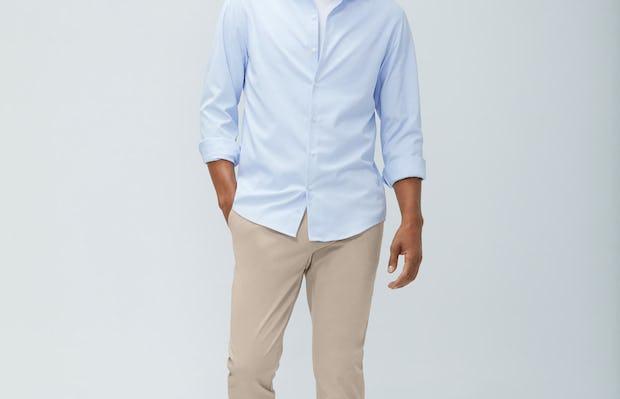 men's light blue aero zero dress shirt and men's desert khaki momentum chino model walking forward with hand in pocket