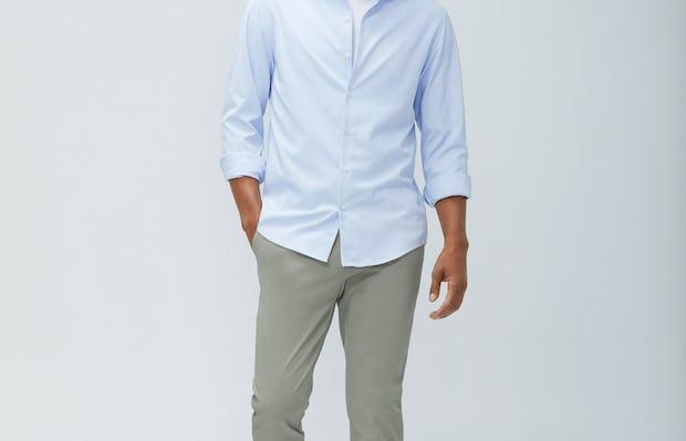 men's light blue aero zero dress shirt and men's olive momentum chino model walking forward with hand in pocket