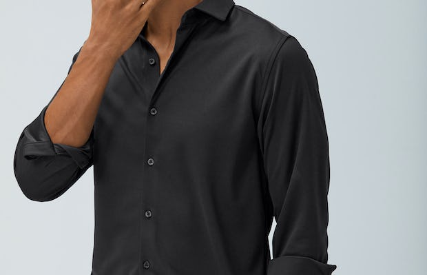 men's black non-brushed apollo dress shirt model with sleeves rolled hand in pocket touching chin