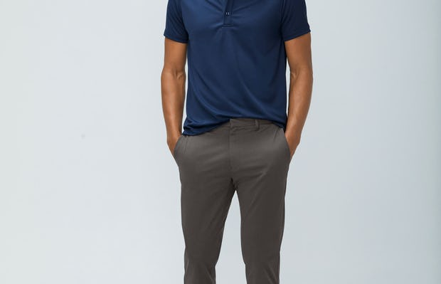 men's navy apollo polo and men's charcoal heather kinetic pant model facing forward hands in pockets