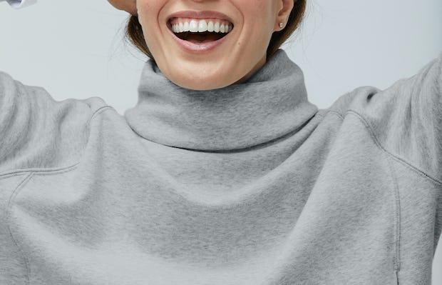 Close up of Women's Marble Hybrid Funnel Neck on model adjusting hair