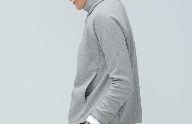 model wearing marble hybrid funnel neck fleece facing left hands in pockets